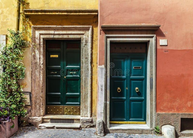 Två klassiska italienska dörrar på väggar målade blått och apelsinen royaltyfri foto
