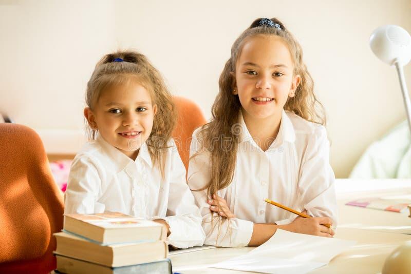 Två klasskompisar som sitter på skrivbordet och att le royaltyfri fotografi