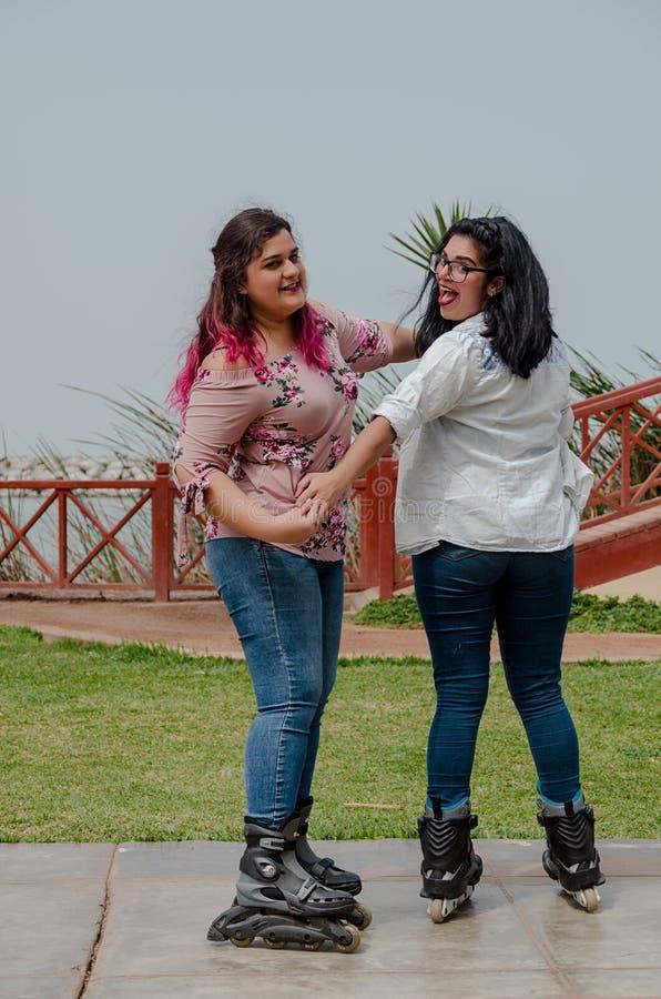 Två knubbiga flickor med inline skridskor i parkera arkivbild