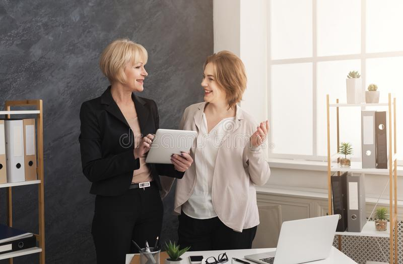 Två kollegor för affärskvinnor som tillsammans arbetar på minnestavlan royaltyfri bild