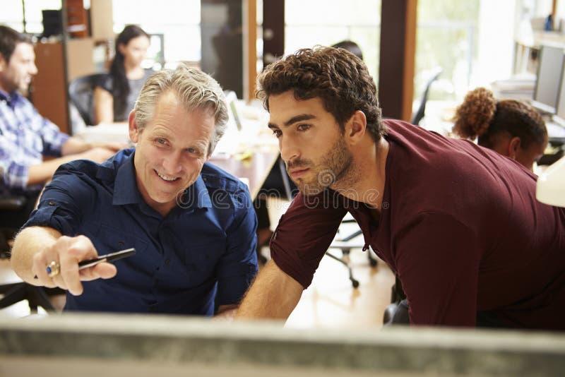 Två kollegor som arbetar på skrivbordet med möte i bakgrund arkivbild
