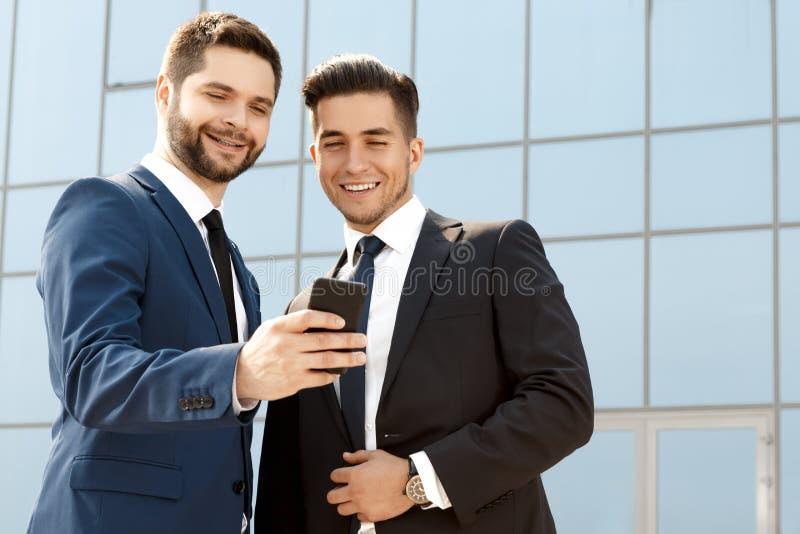 Två kollegor som diskuterar något på en mobiltelefon royaltyfri foto