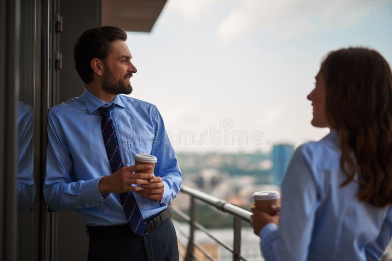 Två kollegor som dricker kaffe på kontorsbalkong royaltyfria foton