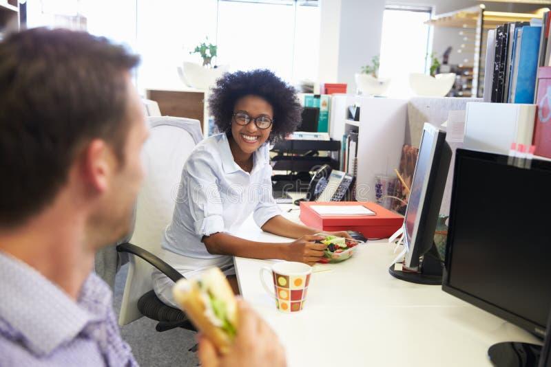 Två kollegor som har ett lunchavbrott på arbete royaltyfria foton