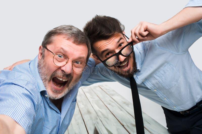 Två kollegor som tar bilden till dem själven som i regeringsställning sitter royaltyfri foto