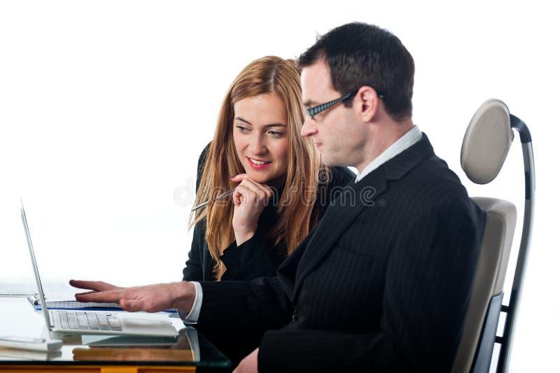 Två kollegor som tillsammans arbetar på en bärbar datordator royaltyfri foto