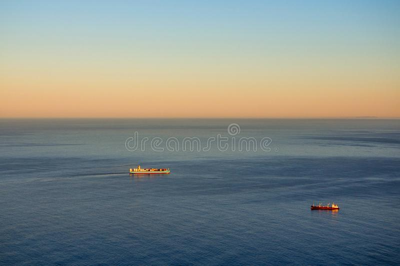 Två kommersiella lastfartyg som navigerar kusten, fodrar av udde till royaltyfri bild