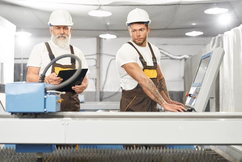 Två kompetenta mekaniker som tillsammans arbetar på metallfabrik royaltyfri fotografi