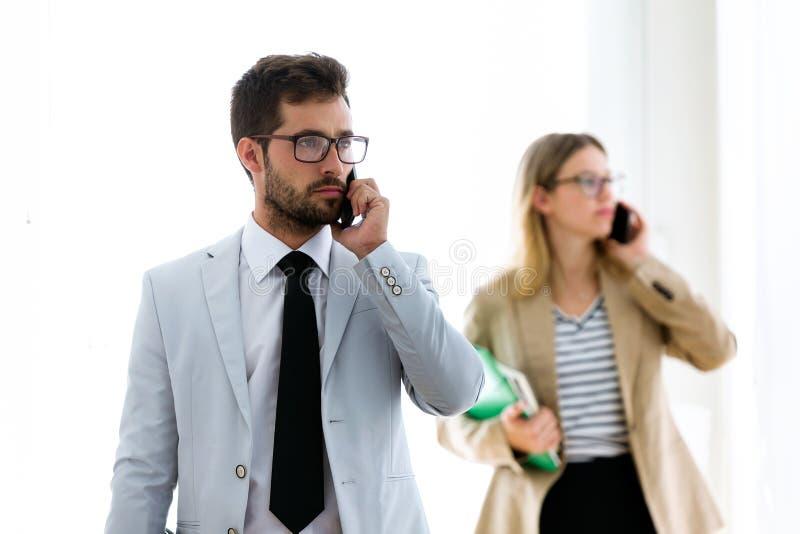 Två koncentrerade unga affärspartners som talar med deras smartphones i ett hall av dem företaget fotografering för bildbyråer