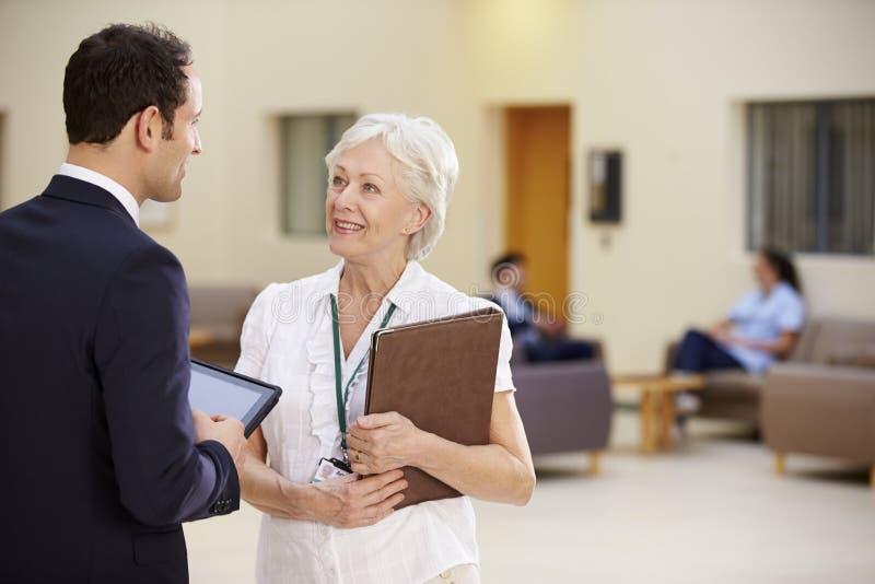 Två konsulenter som diskuterar patientanmärkningar i sjukhus royaltyfri foto