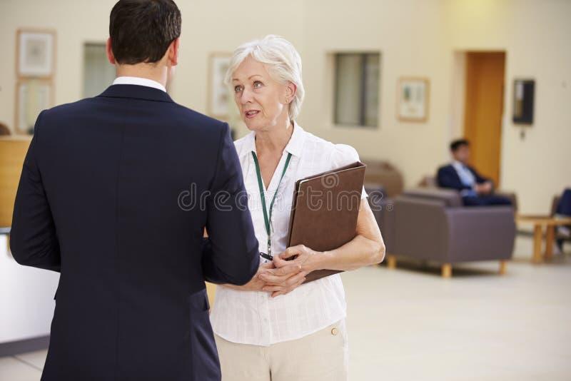 Två konsulenter som diskuterar patientanmärkningar i sjukhus royaltyfri bild