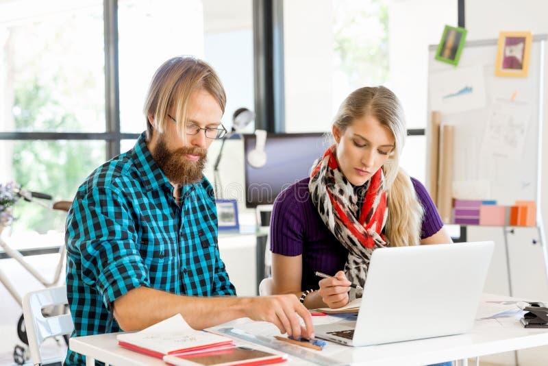 Två kontorsarbetare på skrivbordet royaltyfri foto