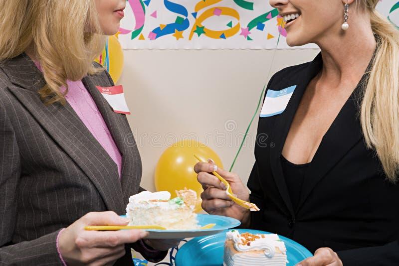 Två kontorsarbetare som äter kakan royaltyfria foton