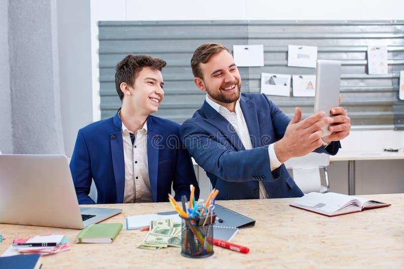 Två kontorsarbetare som ler och gör selfies på mobiltelefoner arkivbilder
