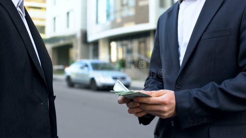 Två kontorsarbetare som räknar pengar utanför affärscentrumet, veckalöndag arkivbilder