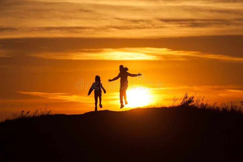 Två konturer av ett barn på solnedgångbakgrund royaltyfria bilder