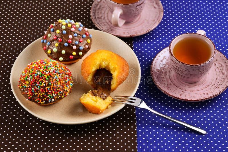 Två kopp te med muffin och choklad med ett mångfärgat pulver på tabellen fotografering för bildbyråer