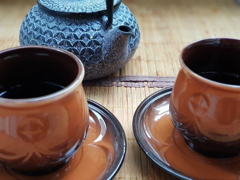 Två koppar av förnyande te med en kokkärl arkivfoto