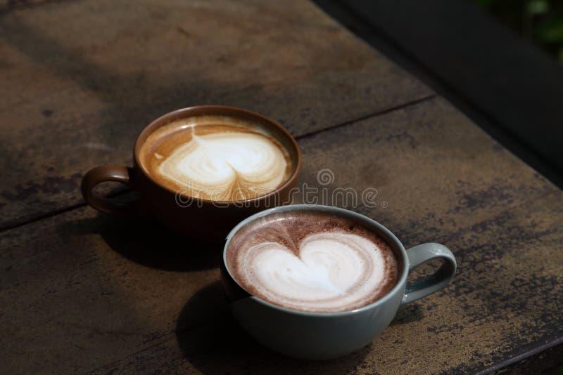 Två koppar av lattekaffe med hjärtaformskum mjölkar på den lantliga trätabellen för att datera parbegrepp med kopieringsutrymme arkivbild