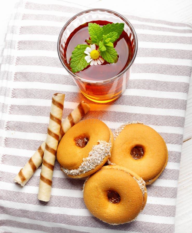 Två koppar av varmt te med läckra kakor på den vita trätabellen royaltyfri bild