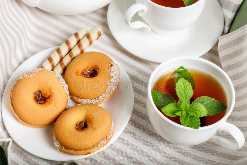 Två koppar av varmt te med läckra kakor på den vita trätabellen royaltyfri fotografi