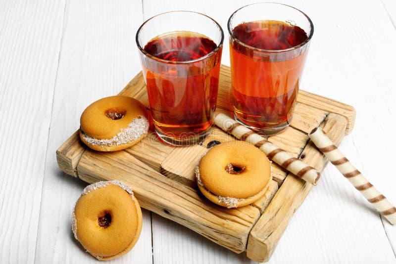 Två koppar av varmt te med läckra kakor på trätabellen royaltyfria foton