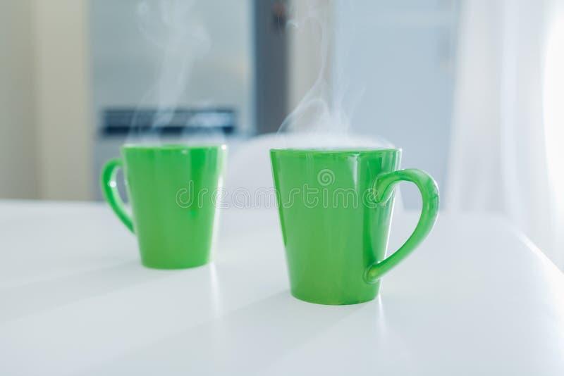 Två koppar av varmt te som ångar på köksbordet royaltyfria bilder