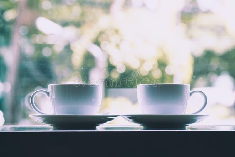 Två koppar för vitt kaffe som tillsammans förlägger royaltyfri foto
