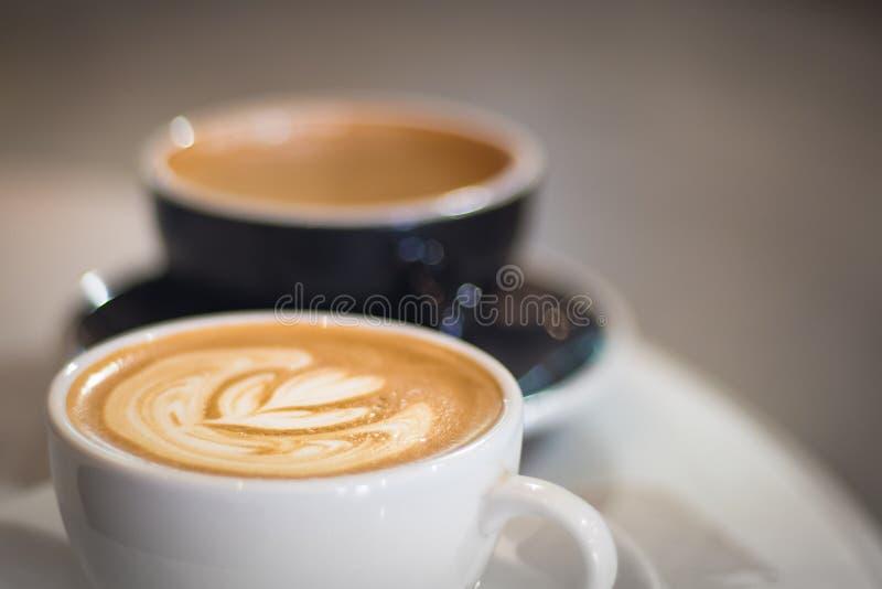 Två koppar kaffe i kafét, vit en med konst för hjärtaformlatte, svärtar en med härlig bokeh som bakgrund royaltyfri bild