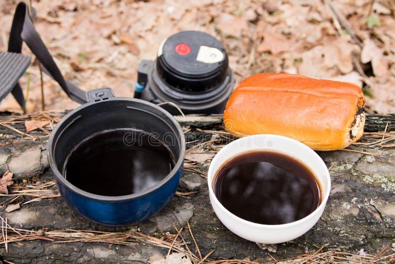 Två koppar kaffe med en bulle söt kopp för giffel för bakgrundsavbrottskaffe Mellanmål i skogen royaltyfri foto