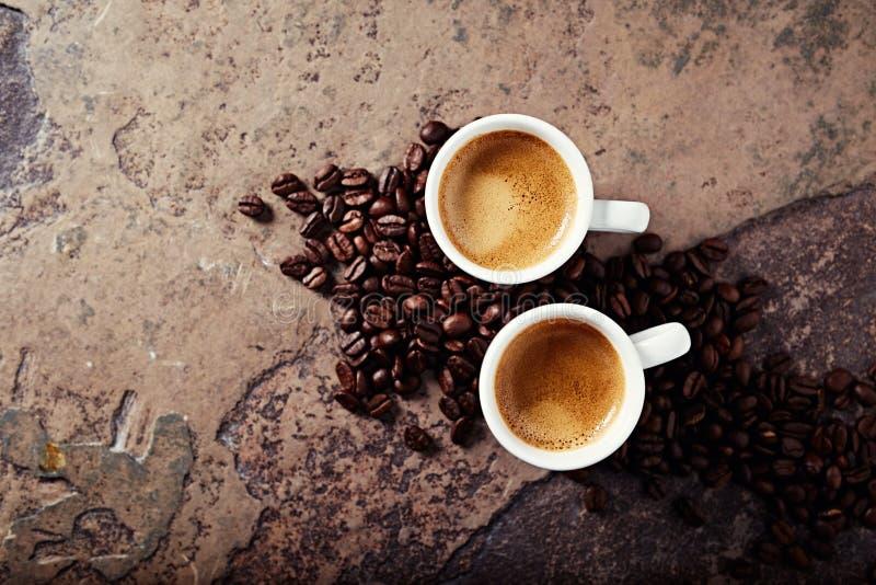 Två koppar kaffe med kaffebönor arkivfoto