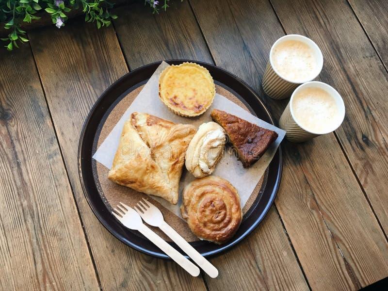 Två koppar kaffe och en platta med brödrullar och kakor spelrum med lampa mobilt foto royaltyfria foton