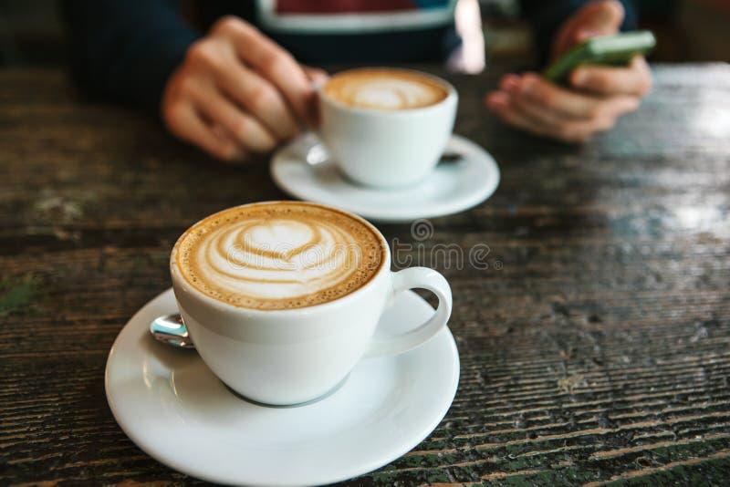 Två koppar kaffe på en trätabell, en man som rymmer en telefon i hans hand och går att kalla Vänta på ett möte arkivbild
