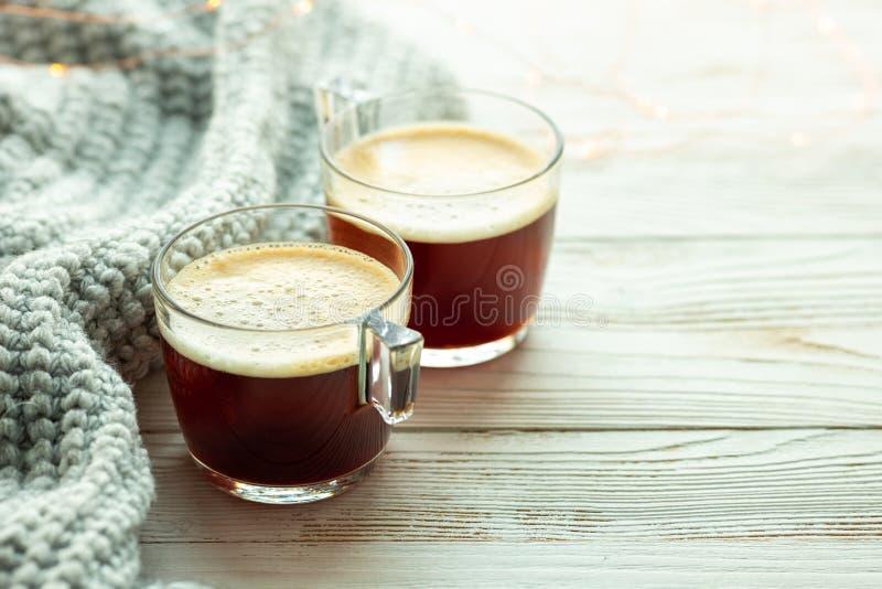 Två koppar kaffe, varm stucken tröja på träbakgrund Varma lampor Hemtrevlig vintermorgon arkivfoto