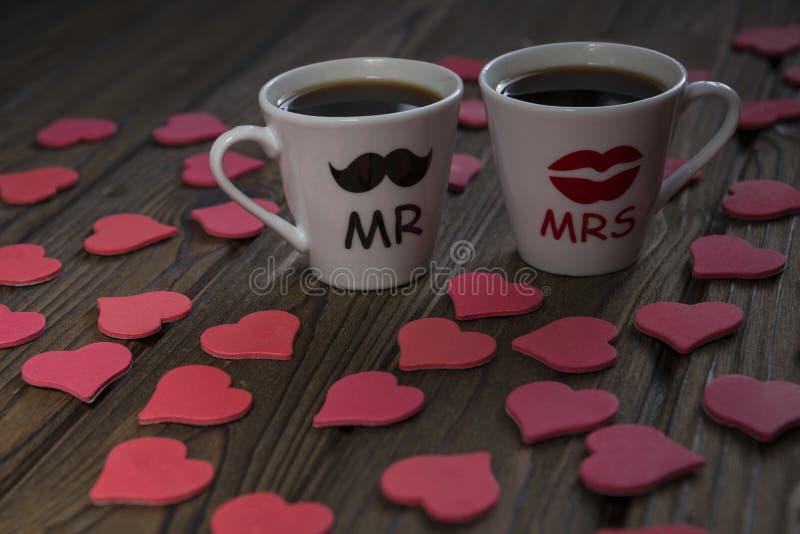 Två koppar med en varm drink av vänner omges av röda hjärtor, arkivbilder