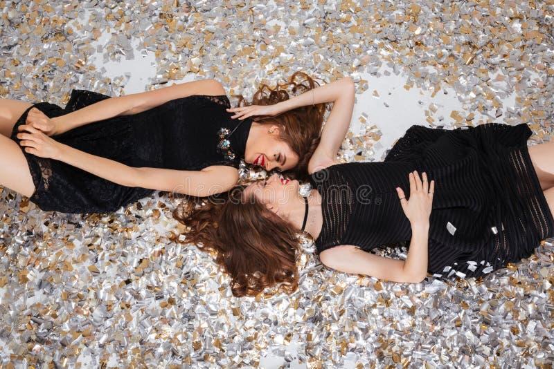 Två kopplade av kvinnor som ligger på bakgrund av mousserande konfettier royaltyfri foto