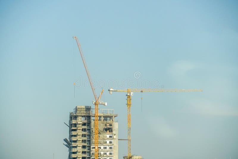 Två kranar bygger byggnaden med blå himmel royaltyfria foton