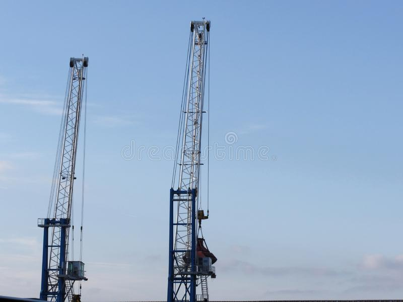 Två kranar för havsport som lyfter gods av däcken med bakgrund för blå himmel royaltyfria foton