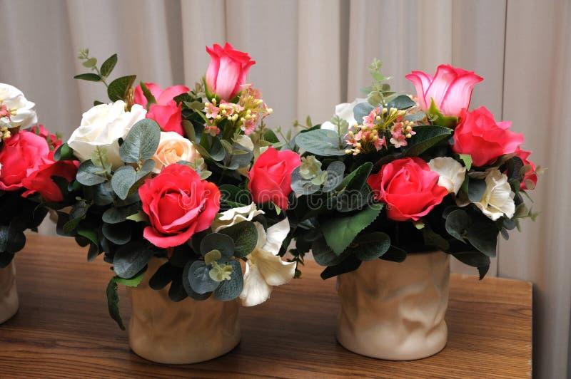 Två krukor av konstgjorda blommor på en trätabell royaltyfri foto