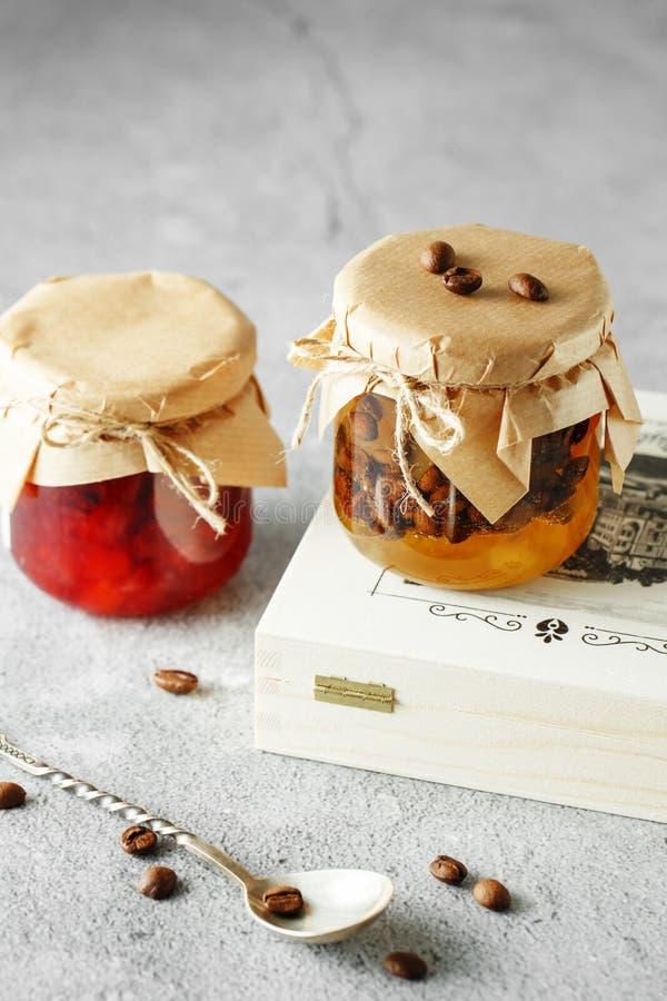 Två krus av hemlagat driftstopp för frukt päronmarmelad med kaffebönor och kruset av blodapelsindriftstopp royaltyfri bild