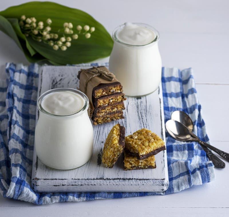 Två krus med hemlagad yoghurt och mellanmål från mysli arkivfoton
