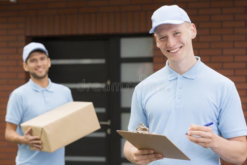 Två kurirer i blåa likformig som framme står av ett hus och väntar med leverans royaltyfri fotografi