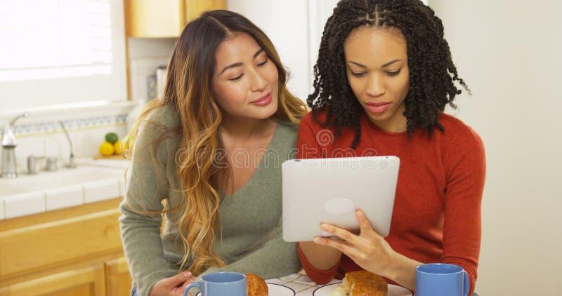 Två kvinnabästa vän som äter frukosten och använder minnestavladatoren royaltyfria foton