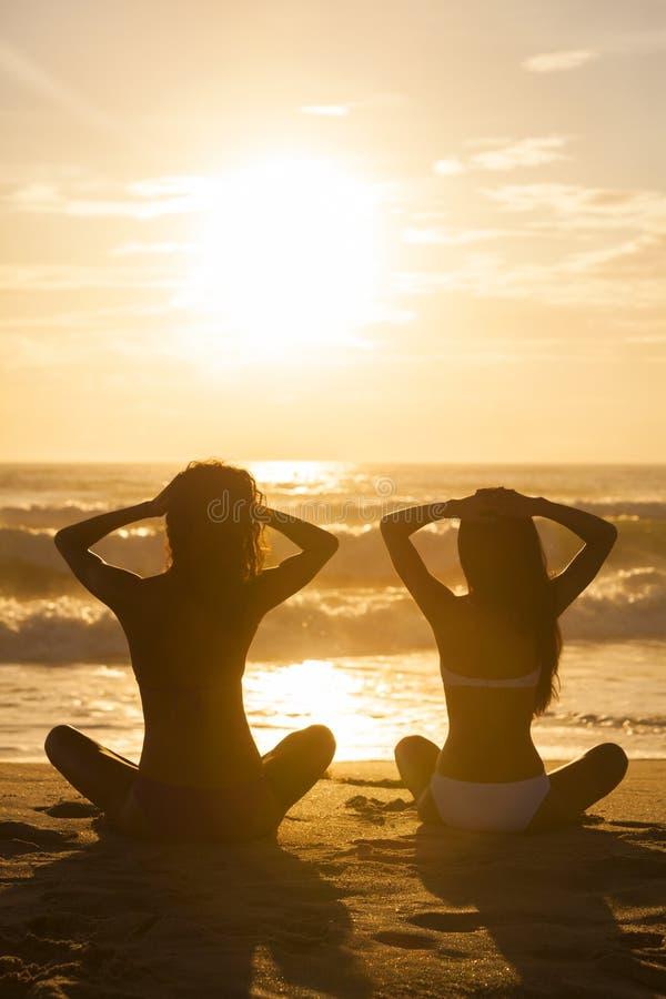 Två kvinnaflickor som sitter stranden för soluppgångsolnedgångbikini arkivbilder