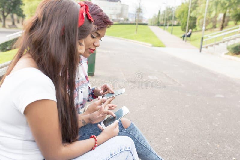 Två kvinnahänder med den smarta telefonen i gatan arkivbilder