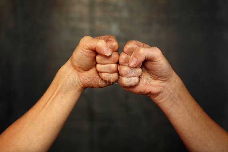 Två kvinnahänder med nävar, i att hälsa gest royaltyfria foton