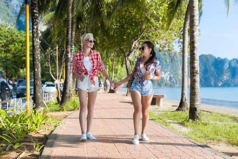 Två kvinnahållhänder som går i tropiska palmträd, parkerar på stranden, härligt ungt kvinnligt par på sommarsemester royaltyfri foto