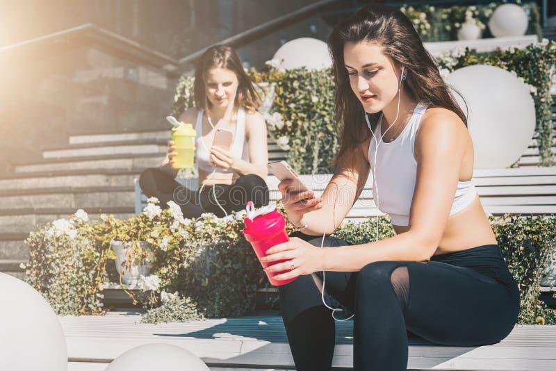 Två kvinnaidrottsman nen i sportkläder sitter på bänk, kopplar av efter sportar som utbildar, använder smartphones, lyssnar till  arkivbild