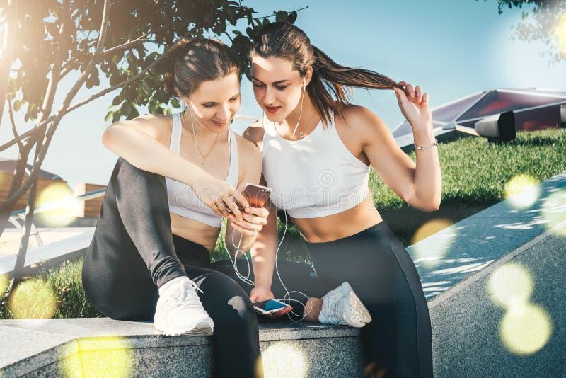 Två kvinnaidrottsman nen i sportswearsammanträde parkerar, kopplar av in efter sportar som utbildar, brukssmartphonen som lyssnar fotografering för bildbyråer