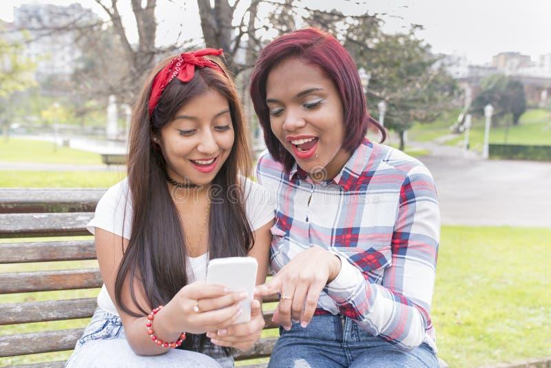 Två kvinnavänner i överraskning som delar socialt massmedia i en smart ph arkivbild